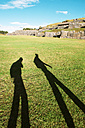 Peru, Cusco, shadow of two backpackers visiting Saksaywaman citadel - GEMF000283