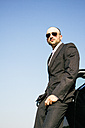 Portrait of businessman with sunglasses ileaning on a car - ABZF000089