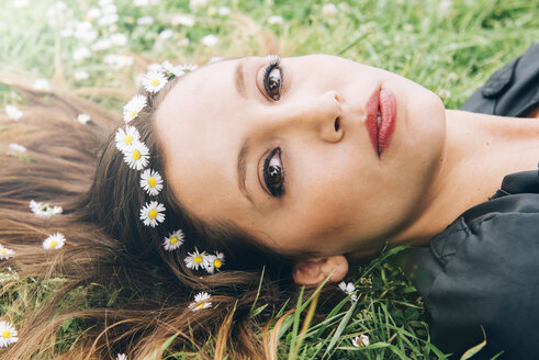 Portrait of young woman lying on grass with daisies in her hair - GEMF000280