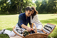 Happy couple having picnic in park - CHAF000749