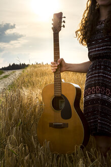 Young woman with guitar in barley field - SARF002055