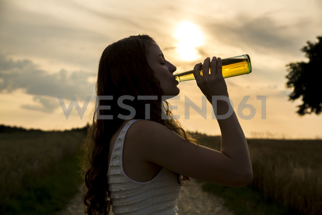 Young woman drinking from glass bottle, evening sonne - SARF002041