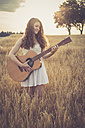 Young woman playing guitar in field, in the evening - SARF002042