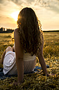 Young woman sitting on field in the evening - SARF002046