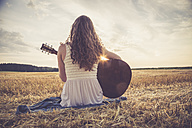 Young woman with guitar sitting on barley field in the evening - SARF002048