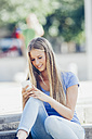 Portrait of smiling teenage girl sitting on steps reading text message on her mobile phone - CHAF000794