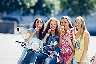 Group picture of four friends with motor scooter and ice cream cones - CHAF000800