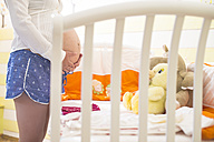 Pregnant woman standing in front of a cot - DEGF000461