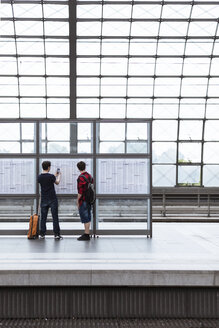 Germany, Berlin, two teenage boys looking at schedule at main station - MMFF000854