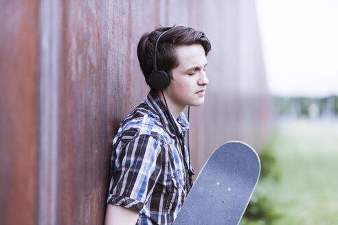 Teenage boy with skateboard leaning on corten wall hearing music - MMFF000864