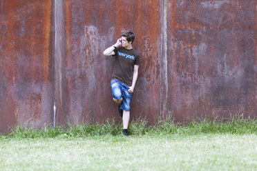 Telephoning teenage boy leaning on corten wall - MMFF000866