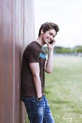 Telephoning teenage boy leaning on corten wall - MMFF000878