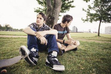 Germany, Berlin, two teenage boys in bad mood sitting under a tree - MMFF000868