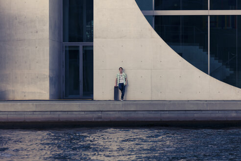 Germany, Berlin, teenage boy with skateboard leaning on facade - MMFF000871