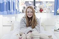Portrait of smiling girl with red hair in hospital bed - ZEF006009