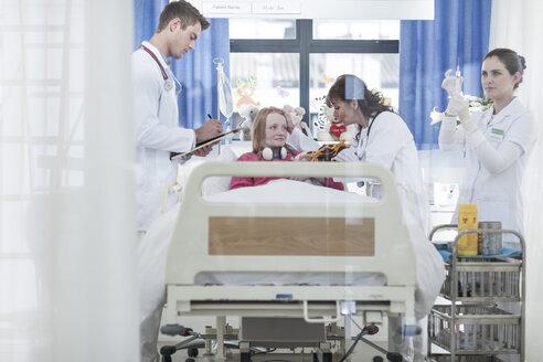 Doctors examining girl in hospital bed - ZEF006012