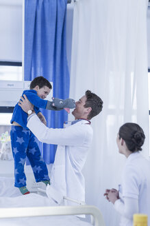 Young doctors playing with little boy in hospital room - ZEF006031
