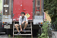 Smiling young man sitting on stairs of a trailer - SGF001781
