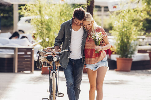 Young couple in love with bicycle and bunch of flowers - CHAF000958