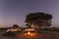 Botswana, Kalahari, Central Kalahari Game Reserve, campsite with campfire under starry sky - FO008276