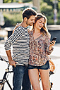 Young lovers with bicycle standing on the street looking at smartphone - CHAF000962