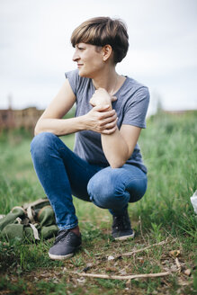 Young woman crouching on a meadow looking at distance - DWF000240