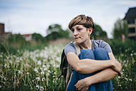 Portrait of young woman sitting on a meadow hugging knees - DWF000243