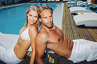 Portrait of couple sitting back to back by swimming pool - CHAF000622