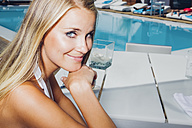 Portrait of smiling blond woman by the swimming pool - CHAF000624