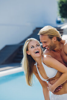 Happy young couple having fun at poolside - CHAF000633