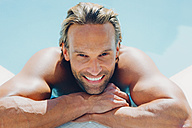 Portrait of smiling man in swimming pool leaning on pool edge - CHAF000638