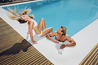 Couple at swimming pool with woman tossing her hair - CHAF000641