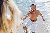 Spain, Majorca, woman pulling man's hand on beach - CHAF000658