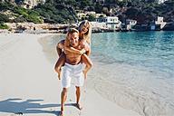 Spain, Majorca, man piggybacking his girlfriend at the sea - CHAF000660