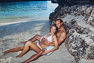 Spain, Majorca, smiling couple leaning against a rock on the beach - CHAF000668