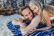 Smiling couple lying on the beach - CHAF000673