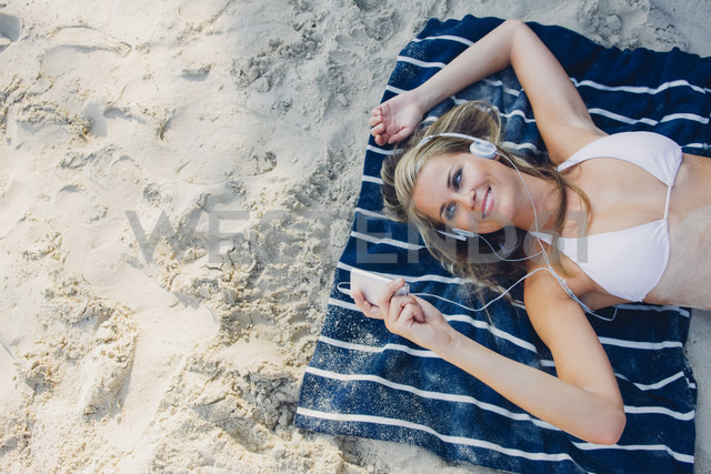 Smiling woman relaxing and listening music on the beach - CHAF000674