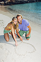 Couple in love on beach drawing heart in sand - CHAF000687