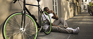 Man sitting on the ground beside his bicycle telephoning with smartphone - RIBF000242
