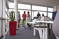 Colleagues in open-plan office standing at the window - RHF000917