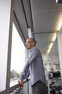 Man in office looking out of window - RHF000925