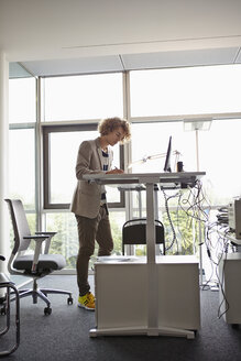 Young man in office working at adjustable desk - RHF000933