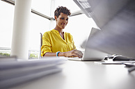 Young woman using laptop in office - RHF000936