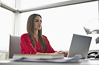 Young woman using laptop in office - RHF000939
