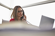 Young woman in office on the phone - RHF000942