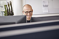 Smiling man in office behind computer screens - RHF000954