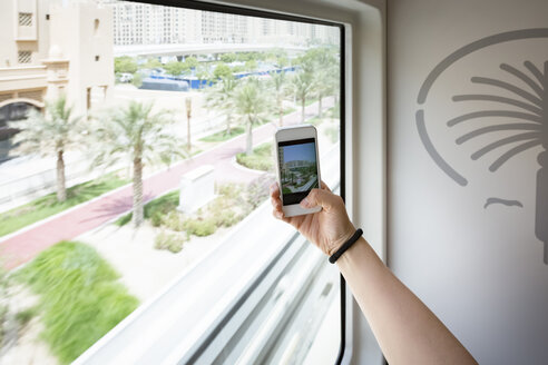 United Arab Emirates, Dubai, women taking photo with her smartphone on the Jumeirah palm monorail - NK000318