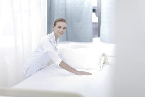 Smiling nurse making hospital bed - ZEF005986