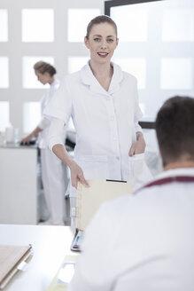 Nurse bringing patient files to doctor - ZEF006039
