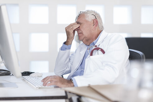Overworked senior doctor sitting at desk working on computer - ZEF006053